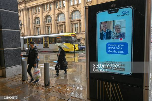 People walk past an electronic sign reminding pedestrians to download the NHS Test and Trace COVID-19 app in Manchester, northern England on October...