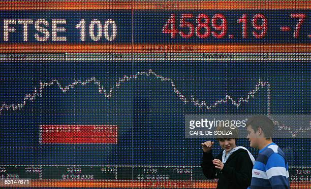 People walk past an electronic sign showing the progress of the FTSE 100 share index in London on October 6 2008 The London stock market nosedived...