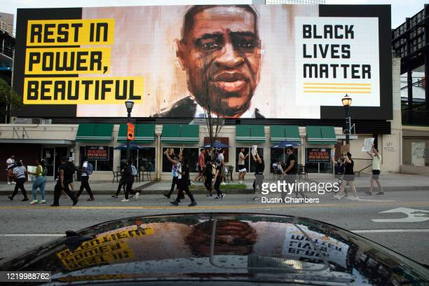 People walk past an electronic sign with an image of George Floyd near Centennial Olympic Park on June 14, 2020 in Atlanta, Georgia. Rayshard Brooks...