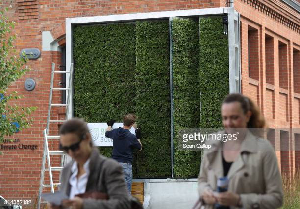 People walk past an employee of German startup Green City Solutions who is putting the finishing touches on a CityTree on July 13 2017 in Berlin...