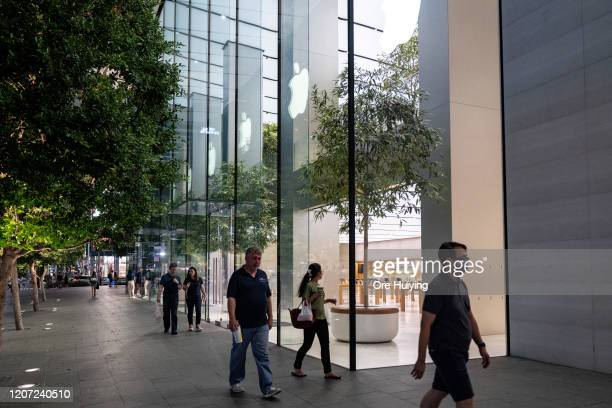 People walk past an empty flagship Apple retail store on Orchard Road on March 15, 2020 in Singapore. The store is temporarily closed after Apple...