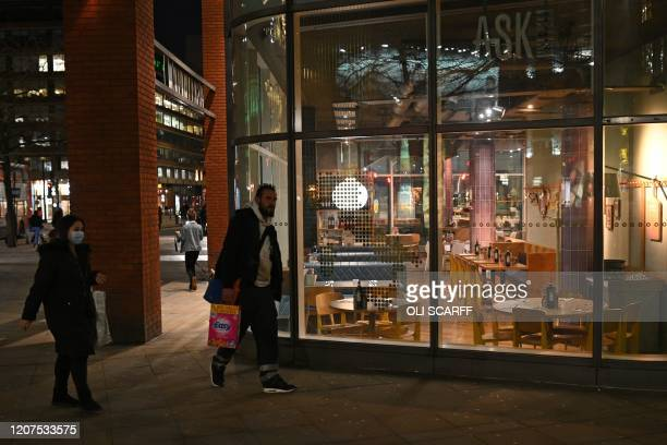 People walk past an empty Italian restaurant in central Manchester on March 17 as Britain's Chancellor of the Exchequer unveils a £330 billion...