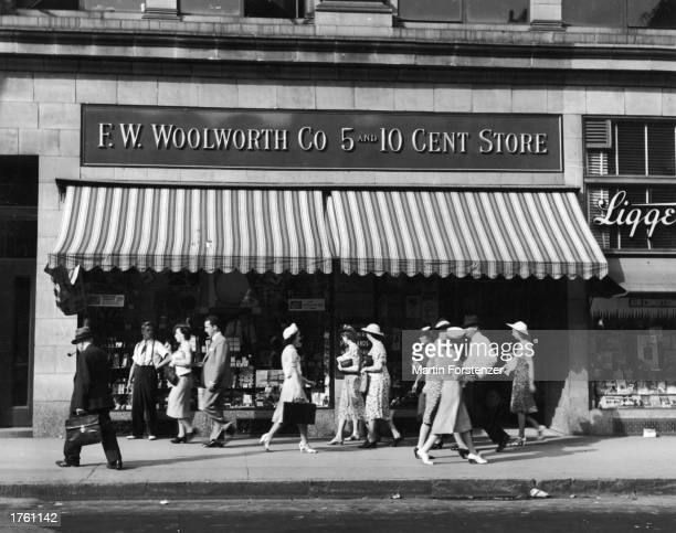People walk past an FW Woolworth five and dime store on a city street 1940s