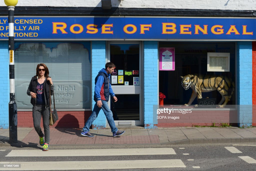 People walk past an Indian restaurant in the town centre of... : News Photo