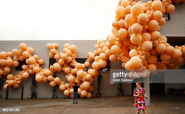 People walk past an installation by renowned LAbased balloon designer Jihan Zencirli aka Geronimo on March 15 2018 in Melbourne Australia The...