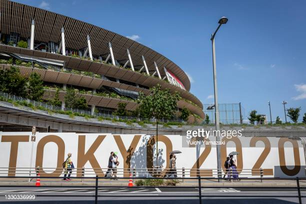 People walk past an Olympics branded wall outside of Olympics Stadium on July 24, 2021 in Tokyo, Japan. As the postponed Tokyo Olympics get underway...