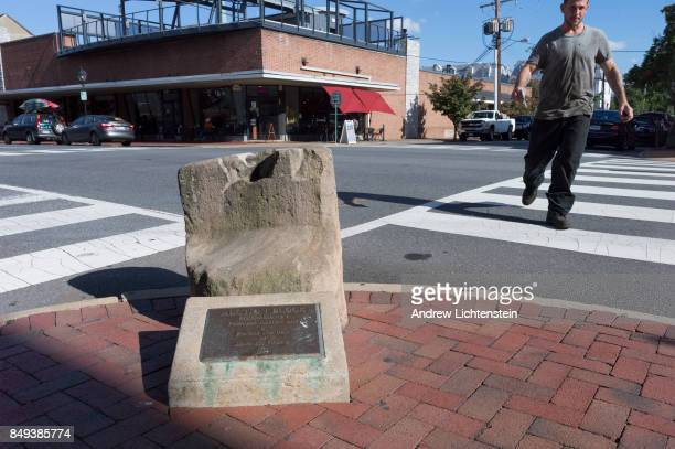 People walk past an original auction bloc used to sell slaves on September 15 2017 preserved in historic downtown Fredericksburg Virginia