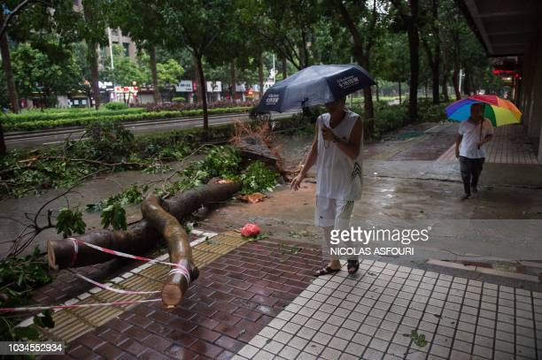 People walk past an uprooted tree a day after super Typhoon Mangkhut in Yangjiang in Guangdong province on September 17 2018 Typhoon Mangkhut slammed...