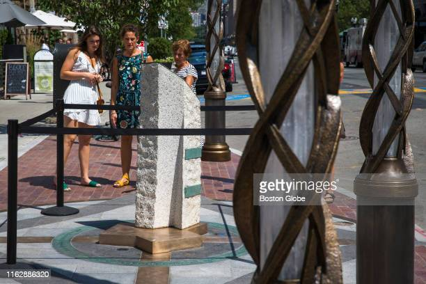 People walk past and observe one out of the three stones commemorating the three people killed in the 2013 Boston Marathon bombings at one of the two...