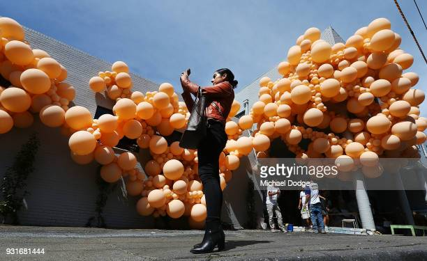 People walk past and photograph the work of Balloon designer Jihan Zencirli aka Geronimo for Melbourne Design Week 2018 on March 14 2018 in Melbourne...