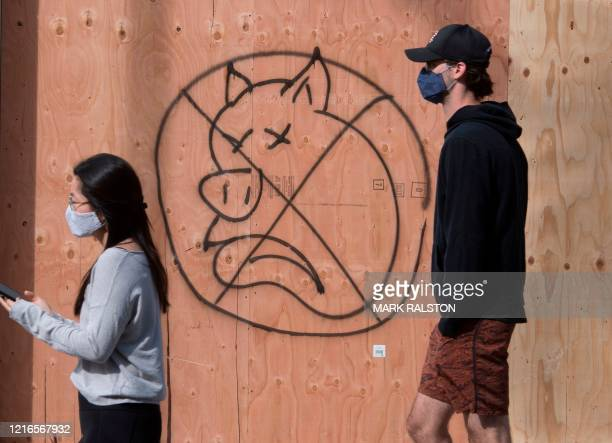People walk past anti-police graffiti outside a store on the iconic Rodeo Drive, after demonstrators protested the death of George Floyd, in Beverly...