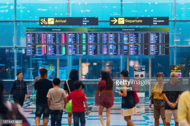 People walk past arrival and departure boards at Terminal 3 of Changi Airport in Singapore on Thursday Dec 13 2018 Singapore'sChangiAirport...