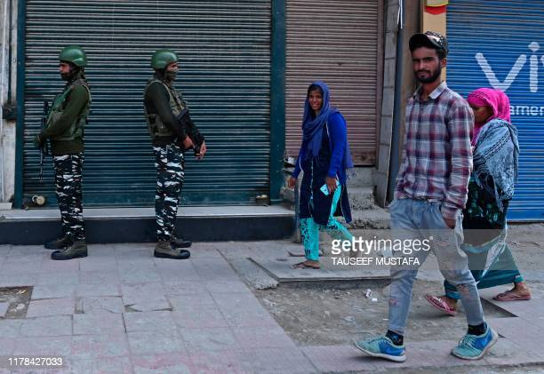 People walk past as Indian paramilitary troopers stand guard during a lockdown in Srinagar on October 27 2019 Kashmiri separatists observe October 27...