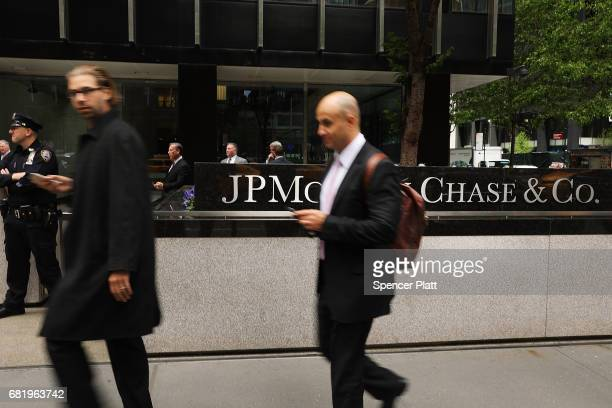 People walk past as others protest outside of the New York City headquarters of JPMorgan Chase on May 11, 2017 in New York City. JPMorgan is one of...