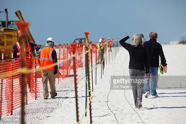 People walk past as workers clean oil leftover from the Deepwater Horizon oil spill in the Gulf of Mexico March 10 2011 at Perdido Key State Park in...