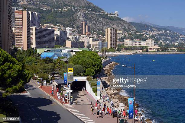 People walk past beyond the placards prior to the UEFA Champions League draw in Monaco on August 27 2014 The 32 clubs 22 of which qualified...