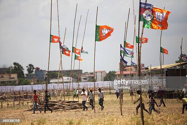 People walk past Bharatiya Janata Party flags on bamboo poles in Muzaffarpur Bihar India on Saturday July 25 2015 More than anywhere Bihar reflects...
