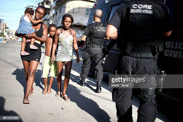 People walk past Brazilian Civil Police patrolling the unpacified Complexo da Mare one of the largest 'favela' complexes in Rio on March 30 2014 in...