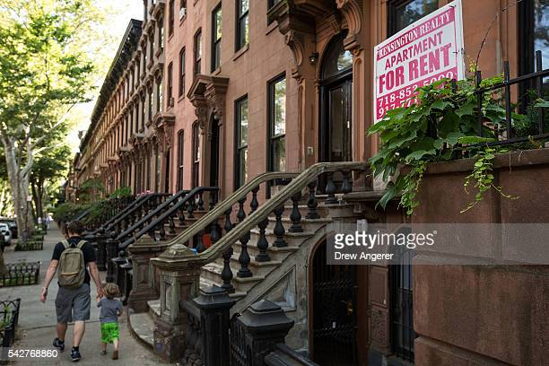 People walk past brownstone townhouses in the Fort Greene neighborhood on June 24, 2016 in the Brooklyn borough of New York City. According to a...