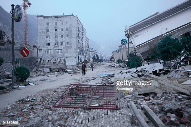People walk past buildings destroyed by an earthquake in Beichuan Sichuan province China on Friday May 16 2008 China has begun the 'longterm' task of...