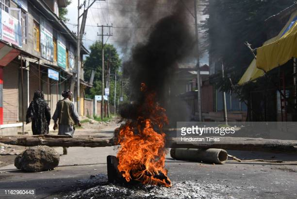 People walk past burning tyres near a barricade set by local protesters to block the road during a protest against the abolishing of Article 370 on...