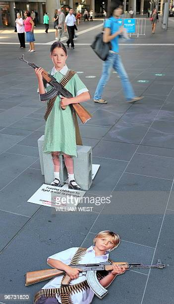 People walk past cardboard cutouts of schoolchildren armed with weapons at Melbourne's Southern Cross train station on February 16 which is part of a...