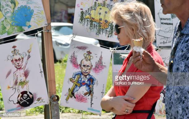 People walk past caricatures of Russian President Vladimir Putin at an openair exhibition by Ukrainian cartoonist architect and journalist Oleh Smal...