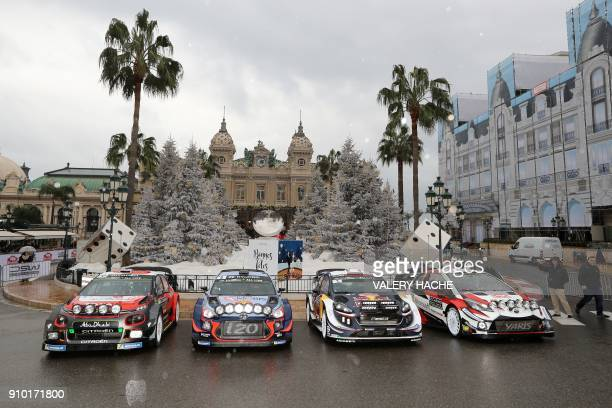 People walk past cars of Citroen Hyundai MSport Ford and Toyota Racing's teams prior to the start of the seasonopening Monte Carlo Rally on January...