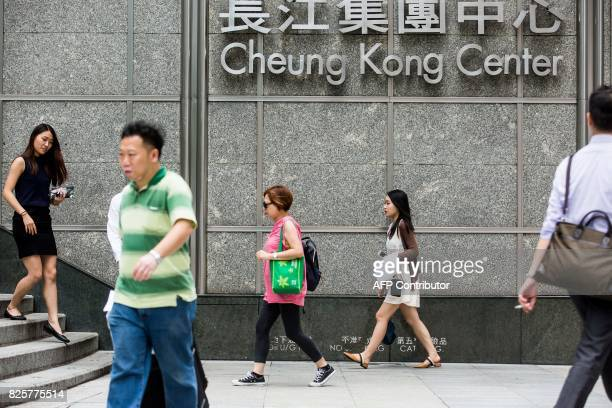 People walk past Cheung Kong Center headquarters of CK Hutchinson Holdings in the Central district of Hong Kong on August 3 2017 CK Hutchinson will...