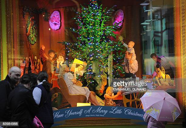 People walk past Christmas decorations set on display at Bloomingdales department store in New York December 10 2008 Despite government figures...
