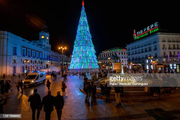People walk past Christmas lights shaped as a Christmas tree at Puerta del Sol Square on November 26, 2020 in Madrid, Spain. The Madrid council has...