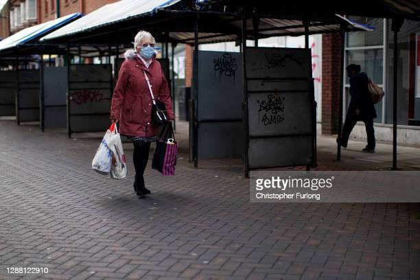 People walk past closed shops and market stalls in Walsall town centre during England's second lockdown on November 27, 2020 in Walsall, United...