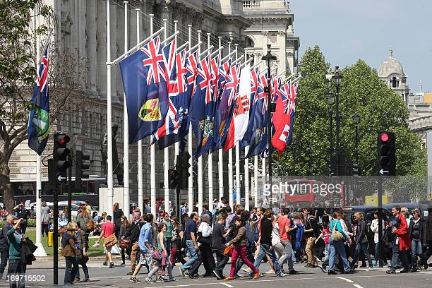 People walk past Commonwealth flags in Parliament Square in Westminster in central London on May 31 2013 Queen Elizabeth II marks the 60th...