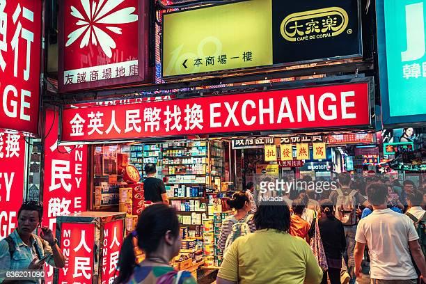 People walk past currency exchange signs in Hong Kong
