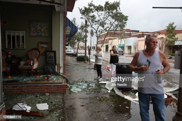People walk past damaged stores after hurricane Michael passed through the downtown area on October 10 2018 in Panama City Florida The hurricane hit...