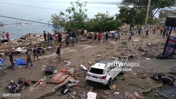 People walk past dead bodies a day after an earthquake and a tsunami hit Palu on Sulawesi island on September 29 2018 Rescuers scrambled to reach...