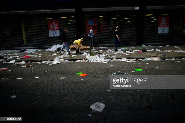 People walk past debris from a looted store during a protest of the death of George Floyd on May 31 2020 in Philadelphia Pennsylvania Protests have...