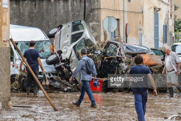 People walk past destroyed cars on October 10 2018 in Sant Llorenc des Cardassar Palma de Mallorca Spain At least nine people have died and nine are...