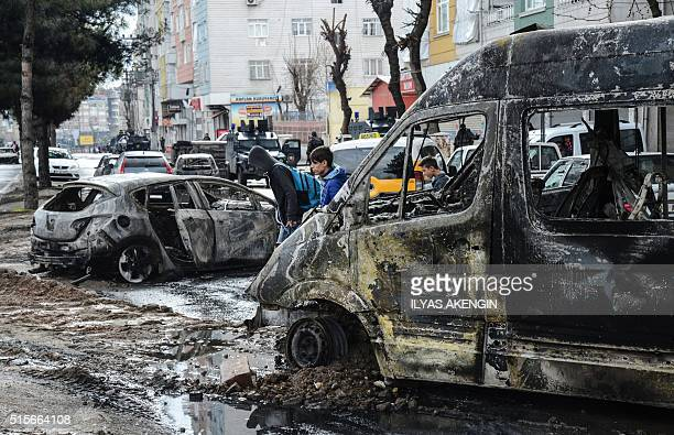 People walk past destroyed vehicles as they leave their houses during clashes in central Diyarbakir on March 15 2016 / AFP / ILYAS AKENGIN