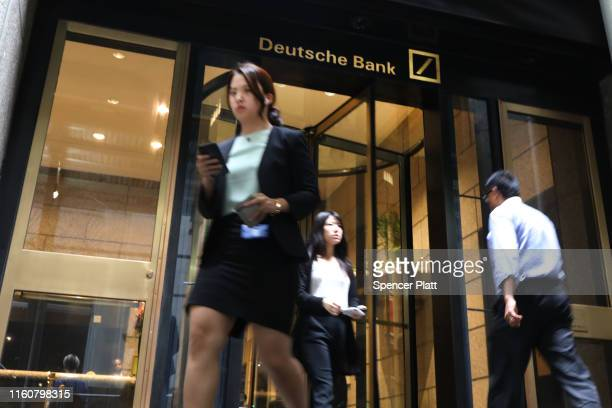 People walk past Deutsche Bank's Manhattan headquarters following news that the global banking giant will be letting go of thousands of employees due...