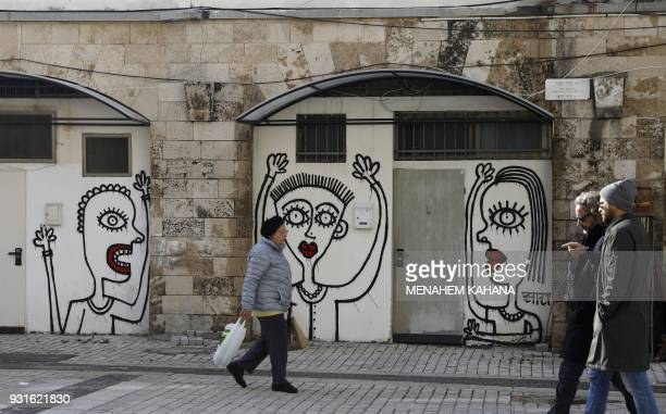 People walk past drawings by New Yorkbased Israeliborn street artist Sara Erenthal in the Israeli coastal city of Tel Aviv on January 28 2018 With...