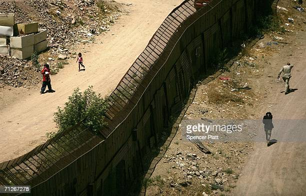 People walk past each other on opposite sides of the fence along the US Mexican border June 21 2006 in Nogales Arizona US President George W Bush...
