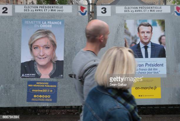 People walk past election campaign posters that show presidential candidates Marine Le Pen and Emmanuel Macron on April 10 2017 in Paris France...