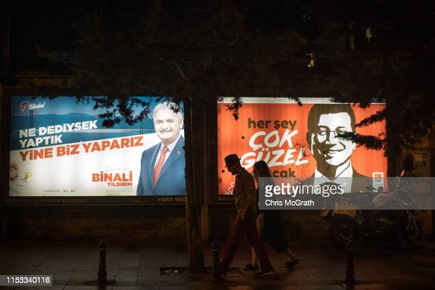 People walk past election posters of AK Parti candidate Binali Yildirim and CHP Party candidate Ekrem Imamoglu during campaigning in the rerun of the...