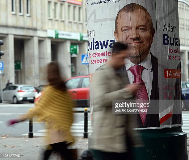 People walk past election posters on a street of Warsaw on October 20 2015 Parliamentary elections in Poland will take place on October 25 with the...