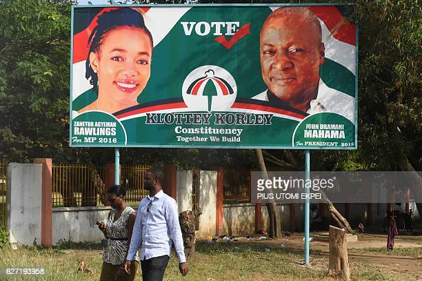 People walk past electoral posters in Accra on December 2 showing the portraits of president and candidate of the ruling National Democratic Congress...