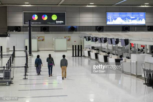 People walk past empty check-in desks at Narita Airport on April 17, 2020 in Tokyo, Japan. Narita Airport, one of Japans busiest, has closed one of...