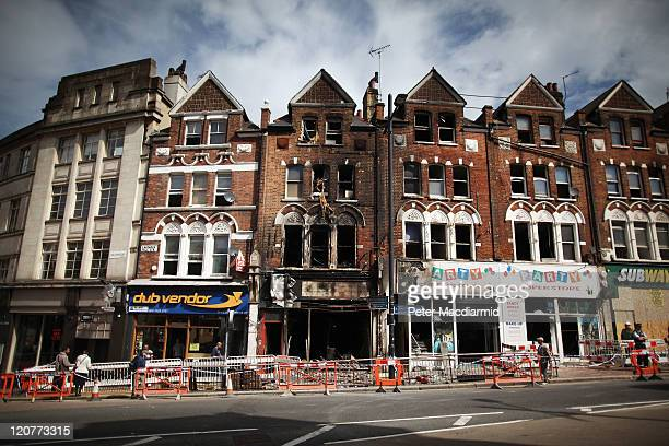 People walk past firedamaged shops and flats in Clapham Junction on August 10 2011 in London England As trouble erupted through the night in other...