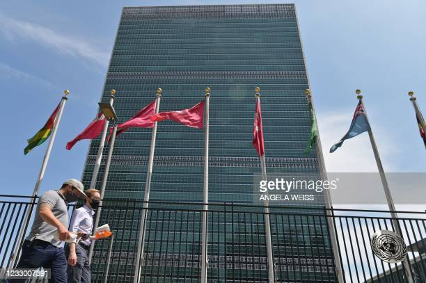 People walk past flags outside the United Nations headquarters on May 20, 2021 in New York City. - Israel faced an escalating conflict on two fronts...