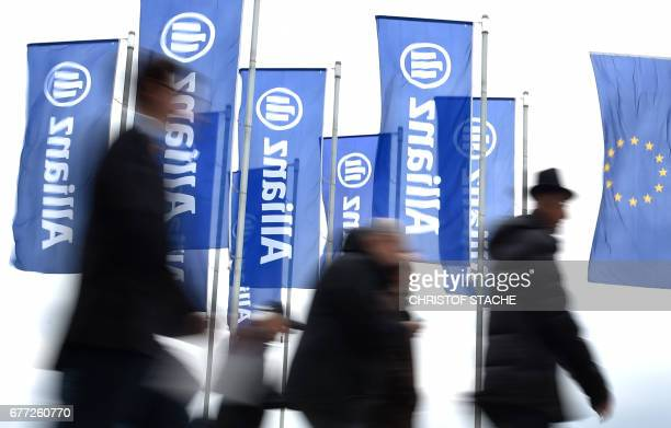 People walk past flags with the logo of German insurer Allianz SE as they arrive to attend the company's annual general meeting in Munich southern...